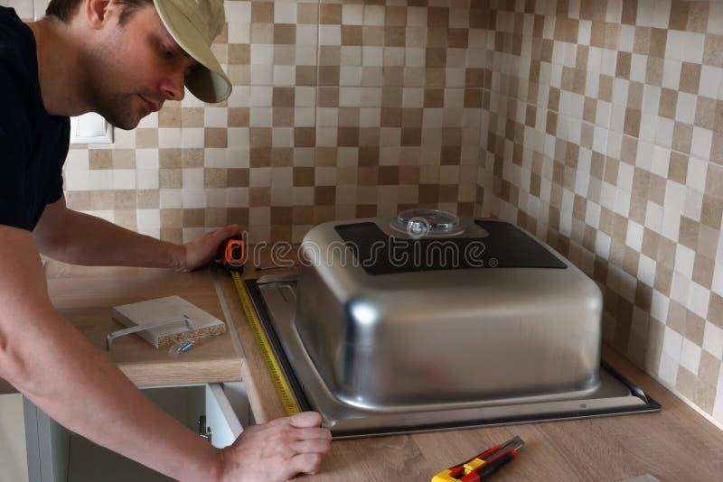 A instalação da banca da cozinha por um mestre na cozinha imagem de stock