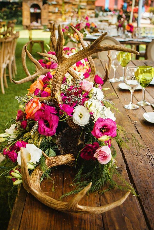 Instalação da tabela, tabela do convidado do casamento, disposição da recepção no coral de vida do pantone e chifres dos cervos imagem de stock