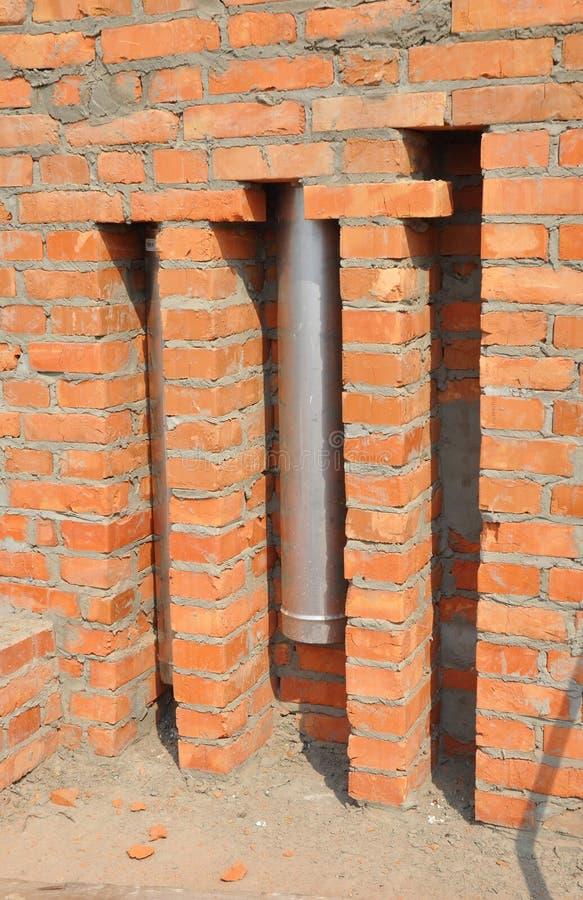A instalação da tubulação da chaminé na parede de tijolo Tubulações e exaustões diretas da chaminé do respiradouro Tubulação coax fotos de stock royalty free