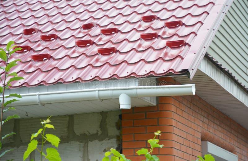 A instalação da tubulação de dreno do downspout da calha da chuva com proteção da placa da neve do telhado do metal imagem de stock