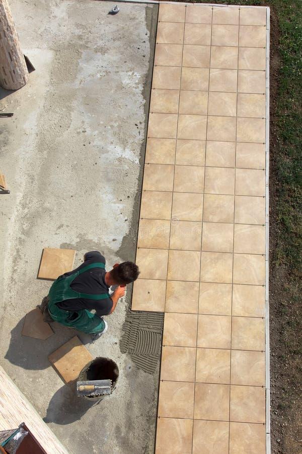 A instalação das telhas de assoalho foto de stock