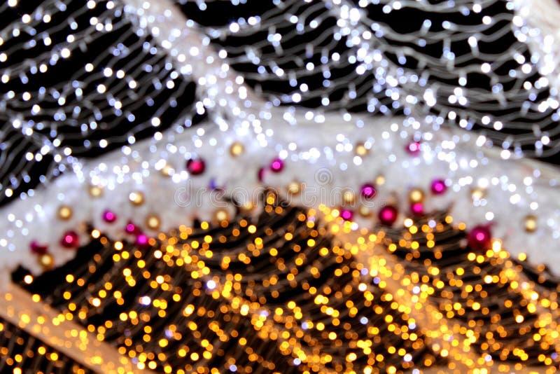 A instalação de decorações do Natal sob a forma das bolas de tons do vermelho e do ouro e de prata e de ouro em defocusing, bokeh imagens de stock royalty free