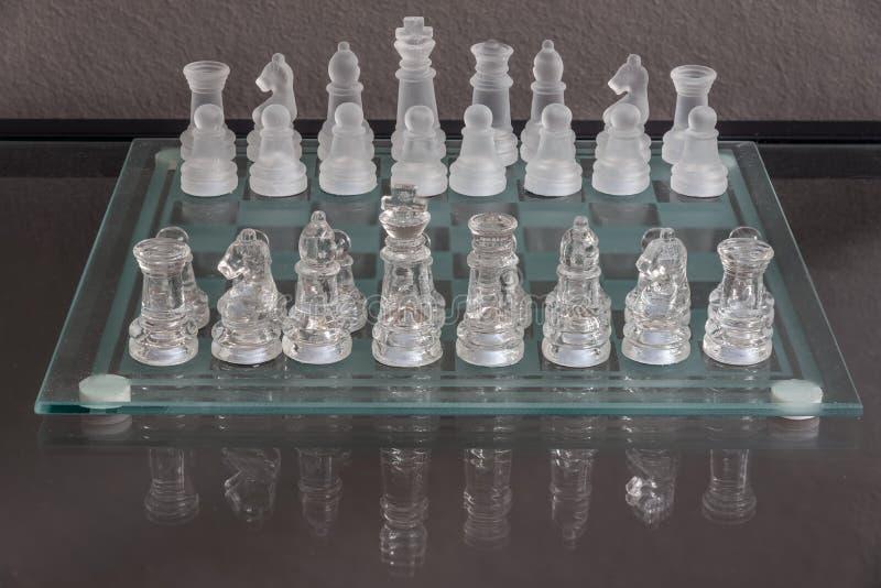 Instalação do começo do jogo de xadrez em um tabuleiro de xadrez de vidro imagens de stock
