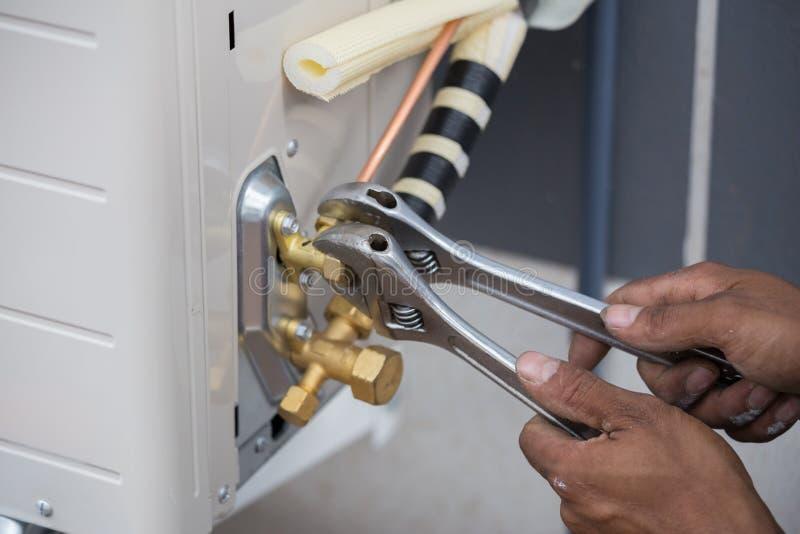 A instalação do condicionador de ar, trabalhador conecta a tubulação de cobre foto de stock royalty free