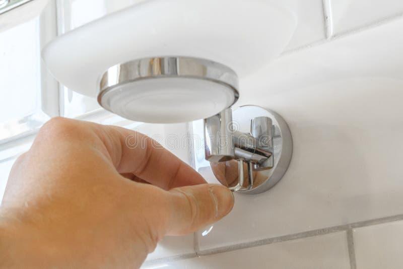 A instalação do suporte de copo no banheiro o conceito do arranjo e reparo de abrigar o espaço imagens de stock