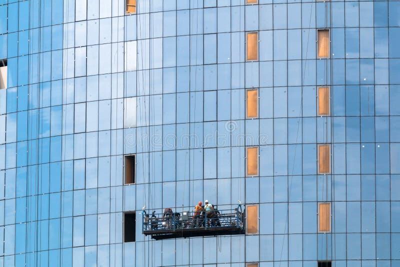A instalação do vidro na fachada de uma construção de vários andares do escritório imagens de stock royalty free