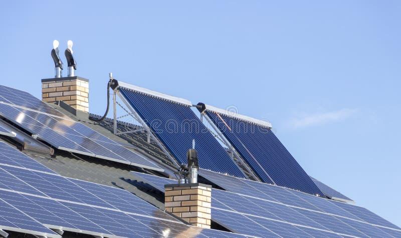 A instalação solar para a geração de aquecimento verde da eletricidade e de água no telhado de um fim residencial da casa acima foto de stock