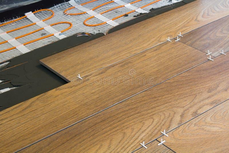 Instalación de baldosas cerámicas y de elementos de calefacción en suelo de baldosas caliente Concepto de la renovación y de la m fotos de archivo
