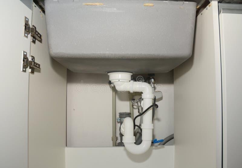 Instalación de cerámica del fregadero de cocina con los tubos de dren de fregadero que sondean fotografía de archivo