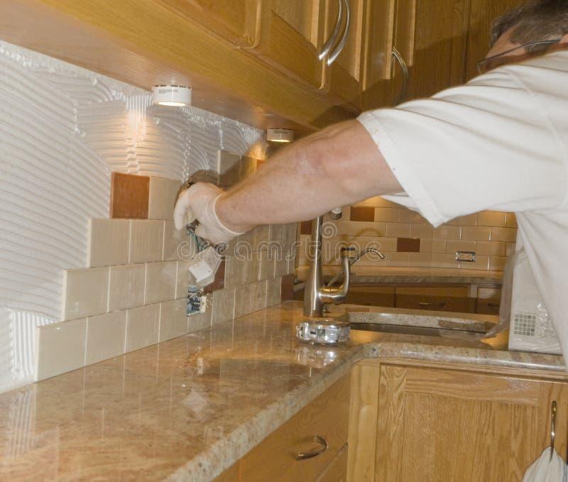 Instalación de la baldosa cerámica en el backsplash 12 de la cocina fotos de archivo libres de regalías