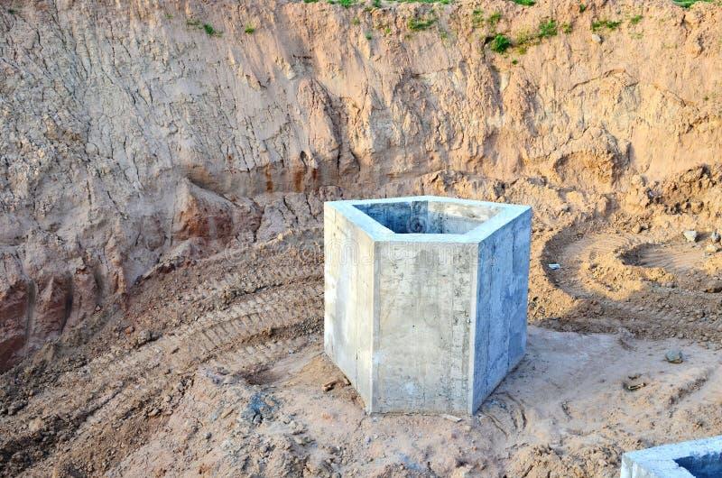 Instalación de los pozos concretos de la alcantarilla en la tierra en el emplazamiento de la obra imágenes de archivo libres de regalías