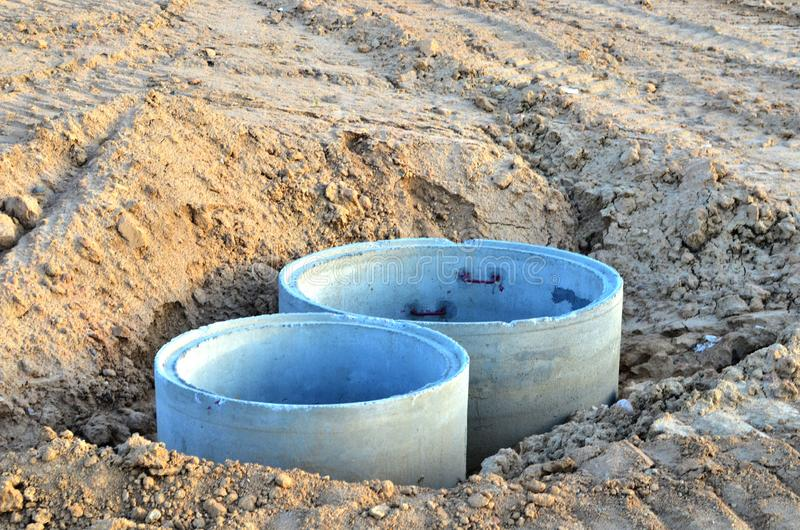 Instalación de los pozos concretos de la alcantarilla en la tierra en el emplazamiento de la obra foto de archivo