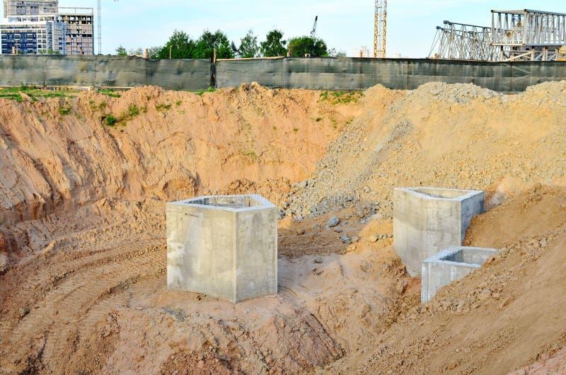 Instalación de los pozos concretos de la alcantarilla en la tierra en el emplazamiento de la obra fotografía de archivo