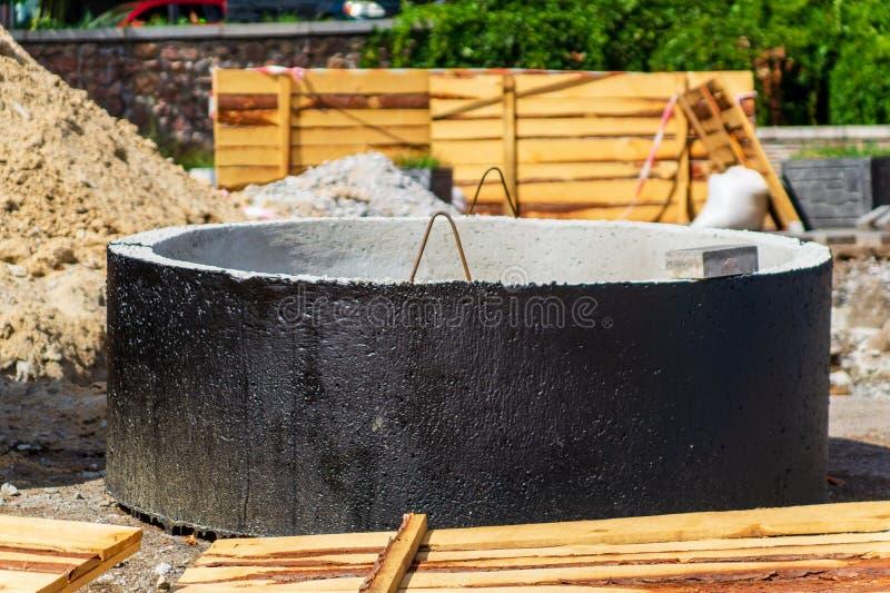 Instalación de los pozos concretos de la alcantarilla en la tierra en el emplazamiento de la obra El uso de los anillos concretos imagen de archivo