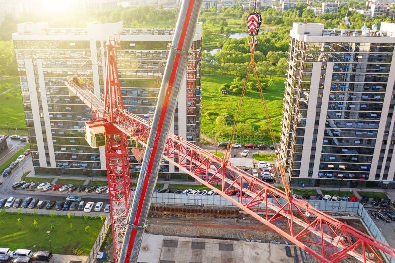 Instalación de una grúa de construcción, con la ayuda de una grúa en un camión, visión aérea En el fondo, visión urbana, residenc imagen de archivo libre de regalías