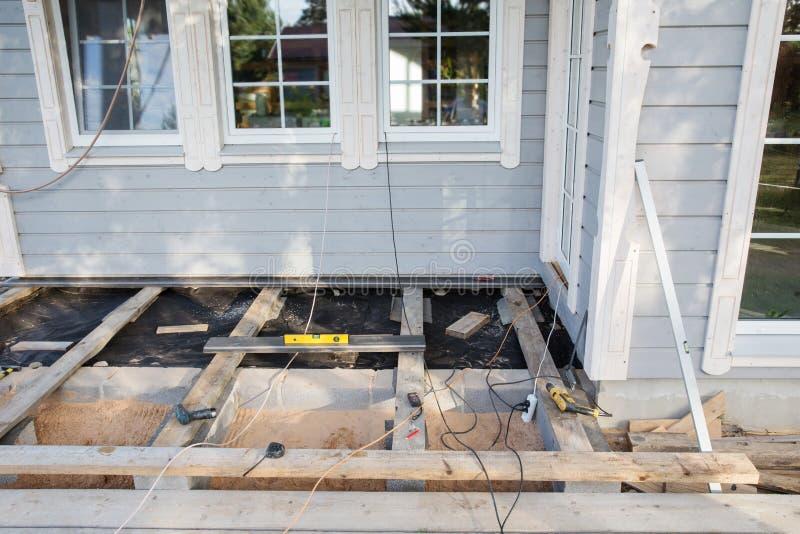 Instalación de una terraza al aire libre del piso de madera en emplazamiento de la obra de la nueva casa fotos de archivo libres de regalías