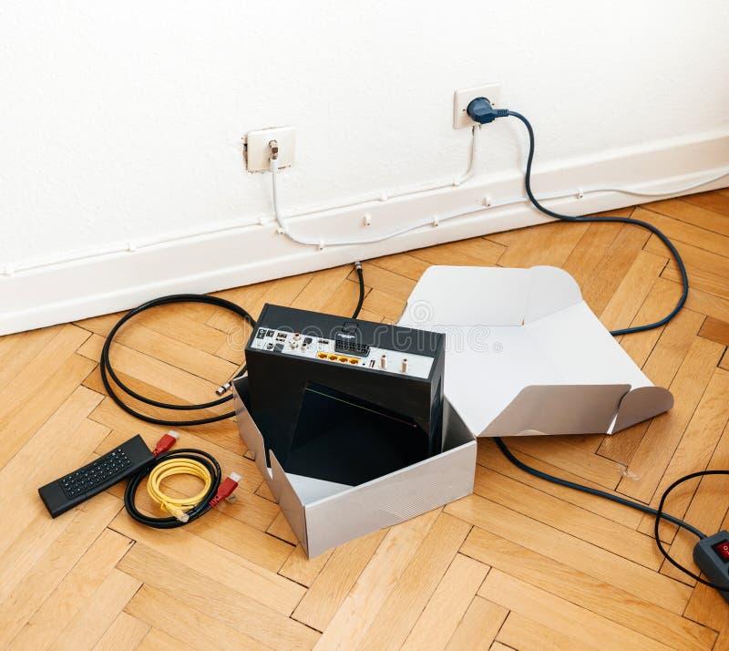 Instalación del módem del proveedor de Internet del cable en piso de madera adentro foto de archivo
