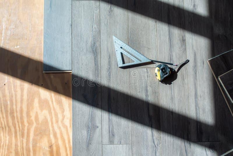 Instalación del suelo y de las herramientas de madera laminados dirigidos para utilizar fotos de archivo libres de regalías