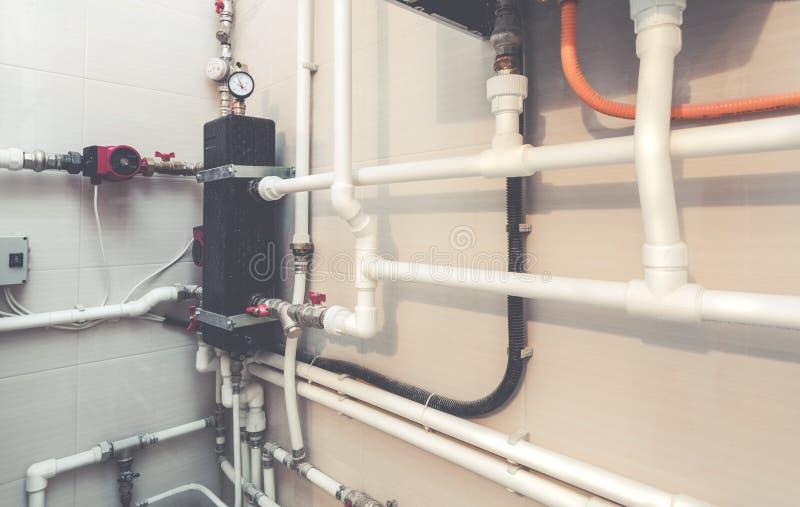 Instalacj wodnokanalizacyjnych klapy z czerwonymi faucets na białych plastikowych wodnych drymbach centrum instalacja wodnokanali fotografia royalty free