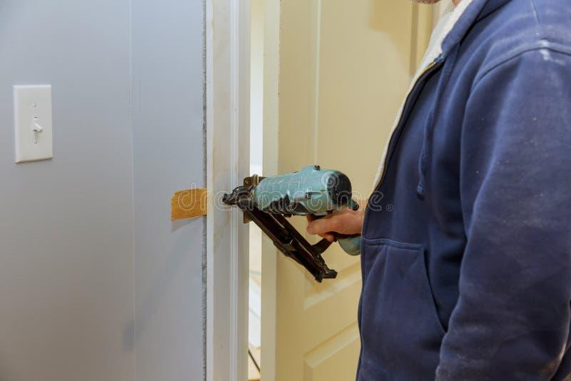 Instalacja drzwi na pracowniku używa lotniczego gwoździa pistolet nowy dom zdjęcie royalty free