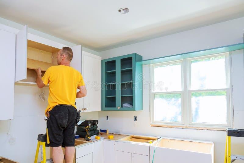 Instalacja kuchnia Pracownik instaluje drzwi kuchenny gabinet zdjęcia stock