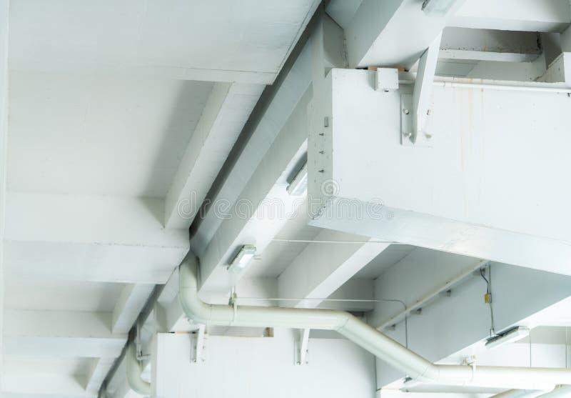 Instalacja wodnokanalizacyjna w centrum handlowym Pionować fajczanego system Budynku wnętrza pojęcie Brudna biała betonowa ściana fotografia royalty free