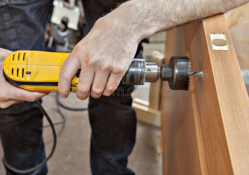 Instalador ao furo de broca sob a fechadura da porta com punho, close-up fotografia de stock royalty free