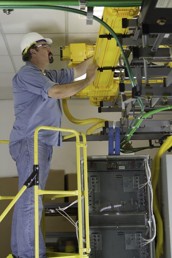 Instalador das telecomunicações na escada do OSHA imagens de stock