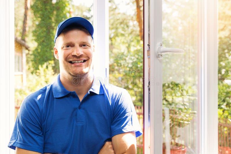 Instalador de la ventana en la situación uniforme del azul en el cuarto imágenes de archivo libres de regalías