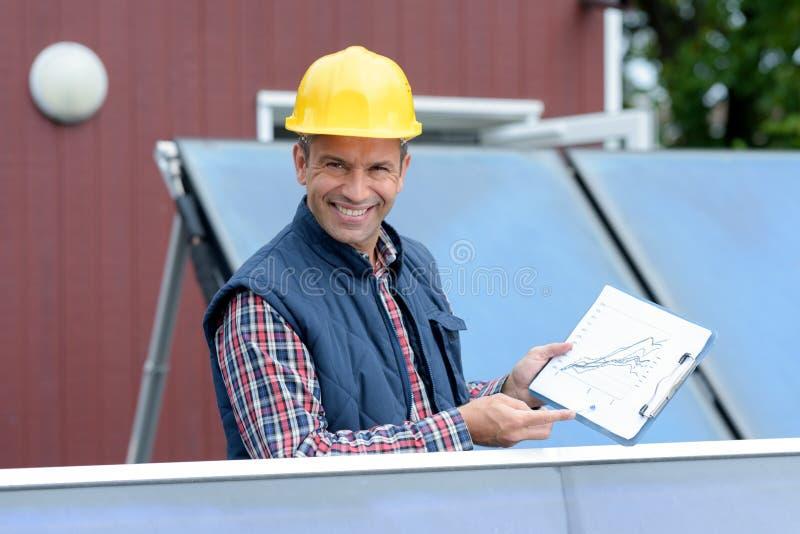 Instalador del panel solar que muestra datos de ahorro foto de archivo libre de regalías