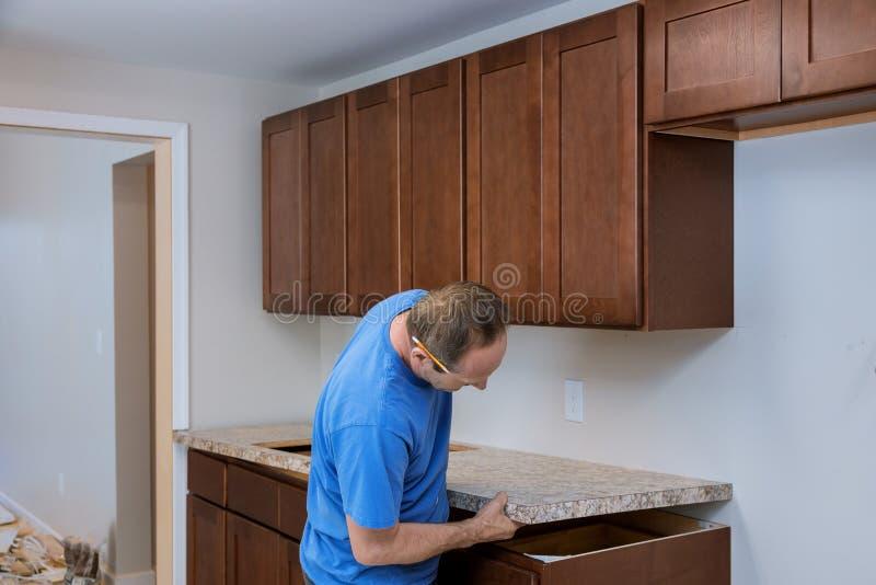 Instalando contratantes uma parte superior que contrária estratificada uma cozinha remodela fotografia de stock