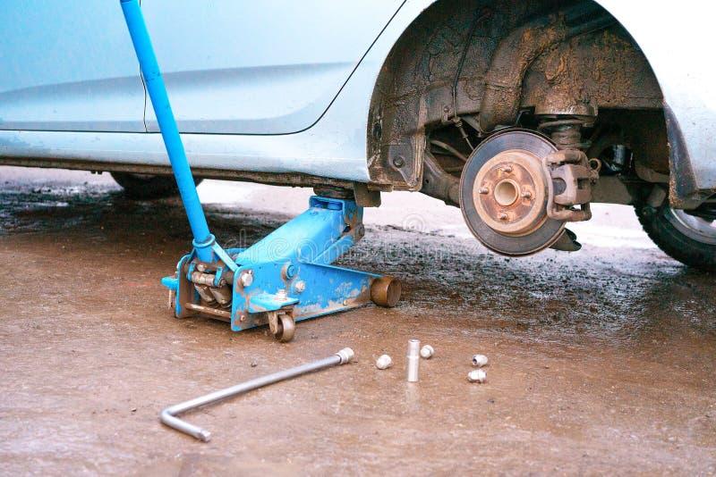 Instalando e para substituir a roda estourada após o impacto na garagem Auto serviço Substituição e manutenção do pneu de carro E foto de stock royalty free