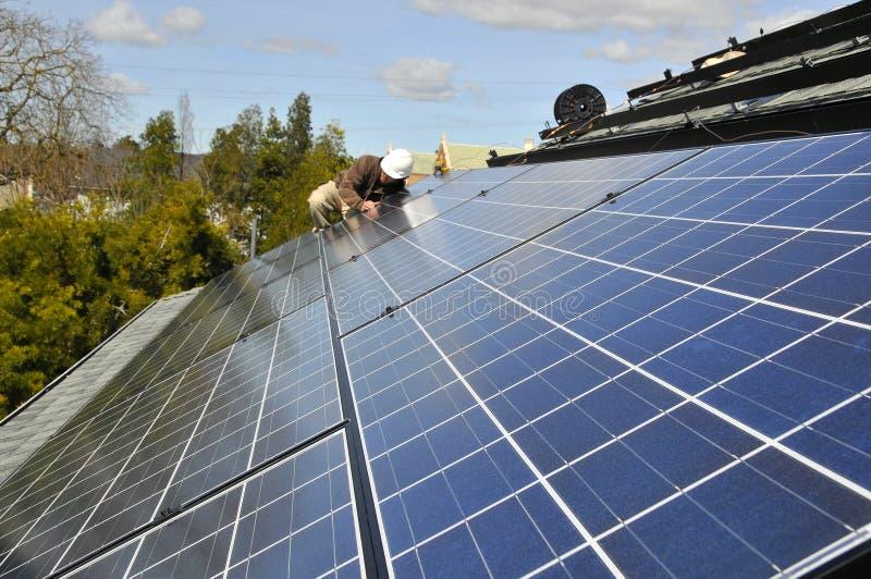 Instalando o painel solar que prende 2 imagens de stock