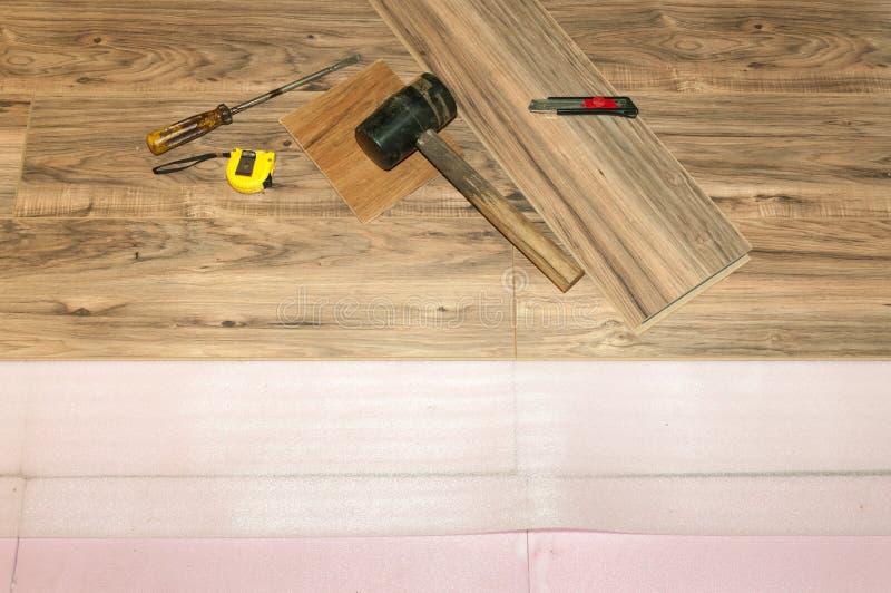 Instalando o revestimento estratificado de madeira com isolação na casa, assoalho novo do ajuste após a inundação imagens de stock