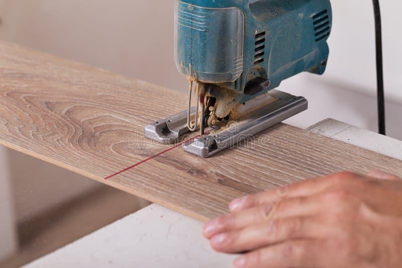 Instalando o revestimento estratificado Placa de assoalho do parquet do corte do carpinteiro imagens de stock royalty free