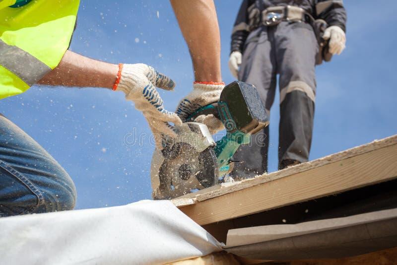 Instalando uma claraboia A circular do uso de Worker do construtor da construção viu para cortar uma abertura do telhado para a j imagens de stock
