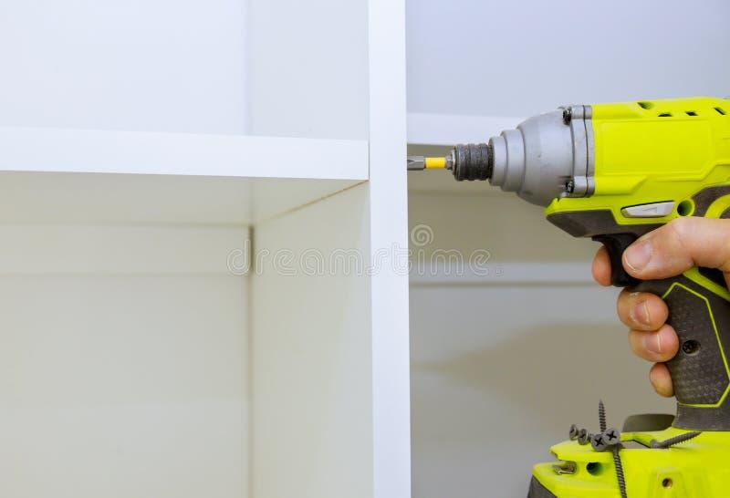 Instalar uma alça de chave de fenda em prateleiras de madeira na parede fotografia de stock