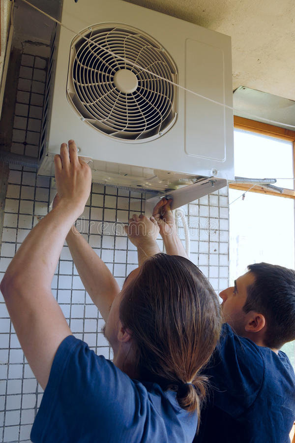Install air conditioning. Two workers install air conditioning stock photography
