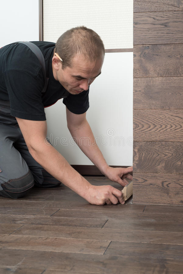 Install baseboards. Male carpenter sets the baseboard on the floor from a massive oak Board stock image