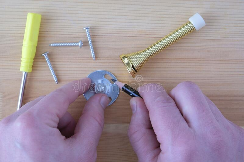 Install the door stopper, hands with a pencil and a screwdriver close-up.  stock images