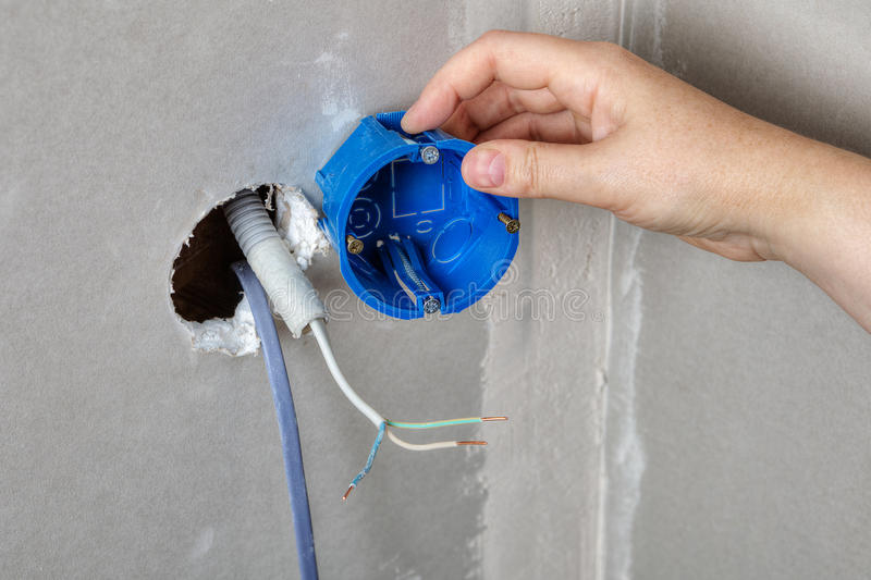 Install electrical box in the wall hole, hand close-up. royalty free stock image