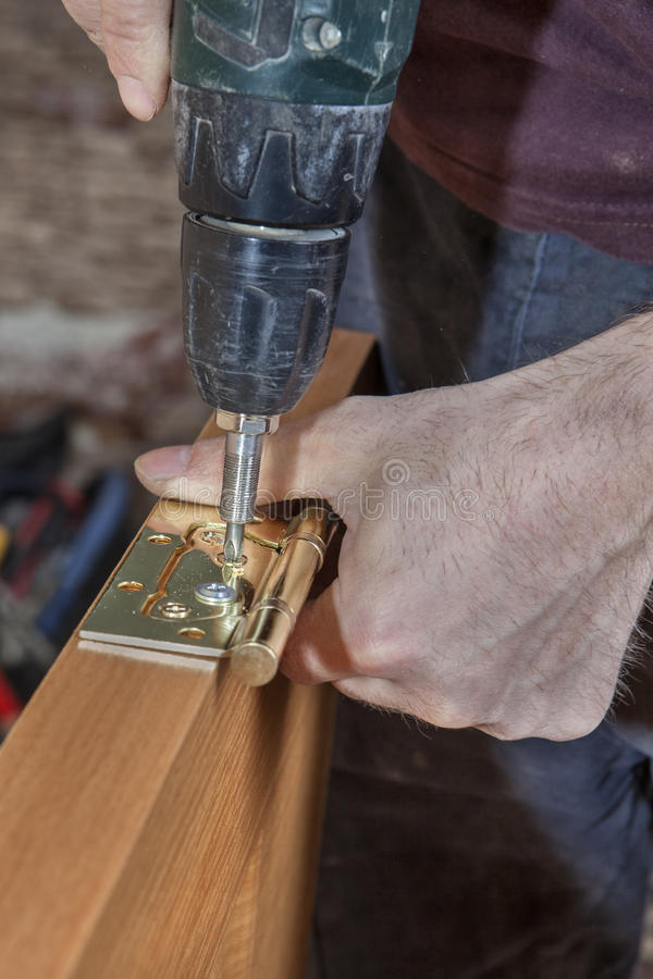 Install hinges for wooden interior door joiner screwing stock download install hinges for wooden interior door joiner screwing stock image image of craftsman planetlyrics Image collections