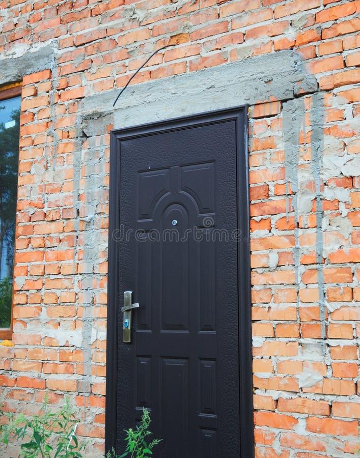 Install metal entrance door in new brick house construction. Install metal entrance door in brick house construction royalty free stock photo