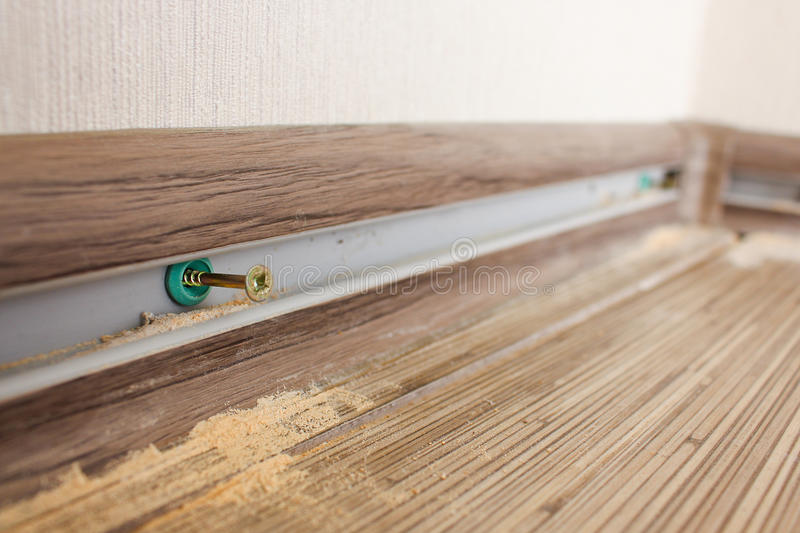 Install new baseboards. Closeup of the and shavings of the fixing plinth stock photography