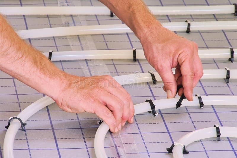 Install under slab heating. Handyman installing the under slab heating in home stock photo
