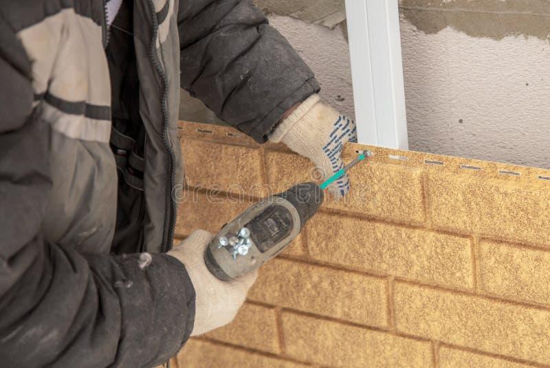 Installando il raccordo del mattone sulla parete della casa immagini stock