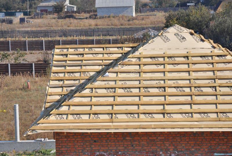 Installando le travi di legno, la gronda, membrana d'impermeabilizzazione, i ceppi e legname sull'angolo del tetto della casa fotografia stock