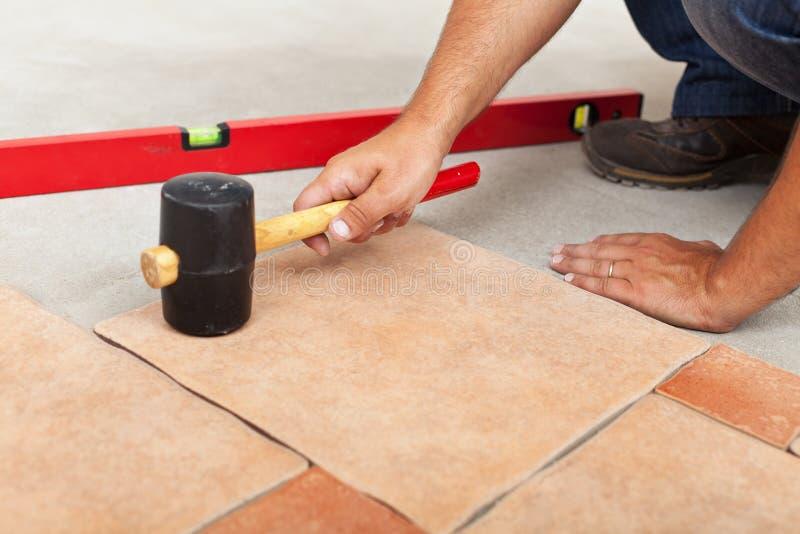 Installando pavimentazione ceramica - misura le mattonelle fotografia stock libera da diritti