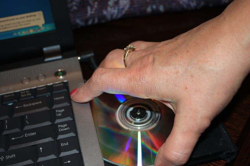 Installando programma dal DVD al computer portatile - immagine fotografia stock libera da diritti