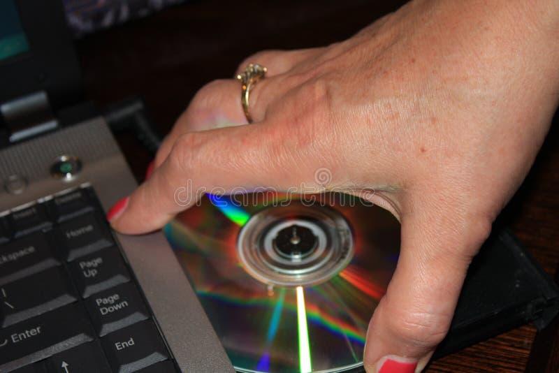 Installando programma dal DVD al computer portatile - immagine immagine stock libera da diritti